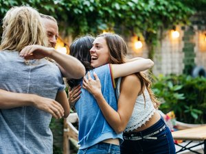 A Group Of Friends Embrace, Excited To See Each Other At Barbecue Meetup
