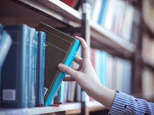 Hand of woman selecting a book from book shelf