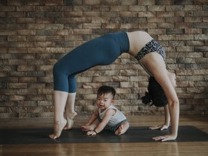 Woman doing an at-home yoga routine with her son on a yoga mat
