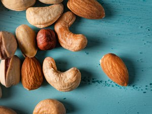 Assortment of nuts in wooden bowl on blue wooden table