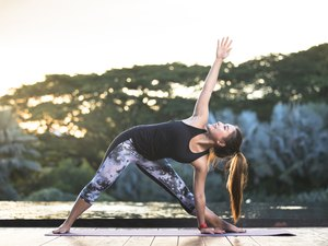woman in black tank top and leggings stretching and practicing yoga outdoors