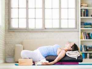Woman using yoga accessories, such as blocks, bolsters and blankets
