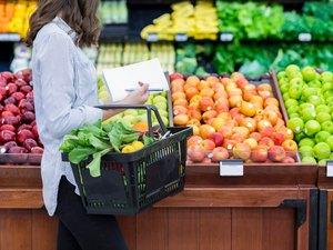 Unrecognizable woman shops for produce in supermarket