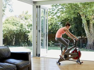 Woman working out on exercise bike at home