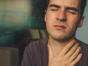Man with a sore throat holding his neck in pain