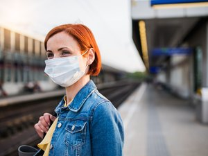 Portrait of young woman wearing protective face mask outdoors in city, waiting for the train.