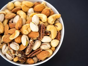 Mixed nuts in a white bowl on a black background.