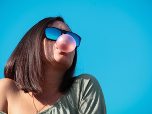 Low Angle View Of Woman Wearing Sunglasses Chewing Gum Blowing a Bubble Against Blue Background