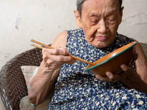 90 up of healthy  old woman having lunch,front view.