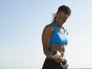 Woman doing a dumbbell biceps curl outside