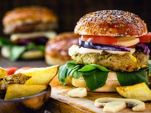 Prepared gluten-free veggie burgers with thick fries on platter.