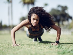 Sporty young woman doing push-ups on lawn