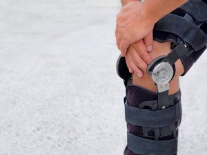 Cropped Image Of Man Wearing Knee Brace While Standing On Land