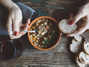Woman eating foods high in sodium like soup and bread