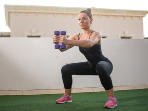 woman doing squats with dumbbells outside in backyard gym