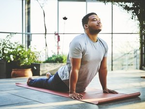 Young man practicing Upward Facing Dog Pose on red mat surrounded by house plants