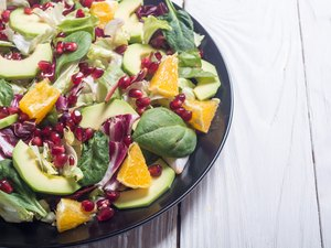 Leafy green salad with avocado, oranges and pomegranates on wooden table