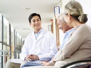 young asian doctor communicating with senior patient