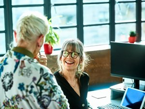 Cheerful mature woman at desk smiling towards senior female colleague