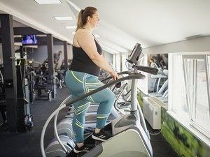 Woman using stepmill for HIIT workout at gym.