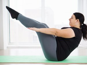 Woman doing Pilates exercises on a mat at home