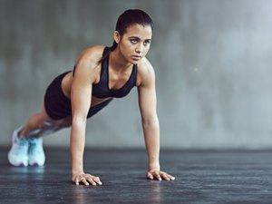 woman in high plank position doing exercises for strong, sculpted arms