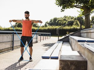 athlete doing resistance band workout outside