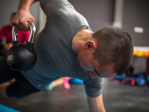 Man lifting kettlebell during ab workout