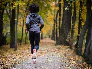 Young woman jogging through the fall park, rear shot.