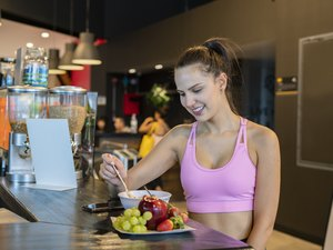 Beautiful young woman eating a healthy bowl and a red apple and more fruit at the gym