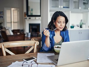 A woman eating a healthy lunch and reviewing her weight-loss program on her laptop