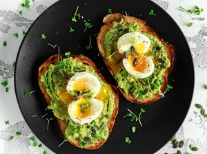 Avocado toast topped with soft boiled eggs