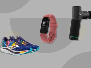 Running shoes, FitBit and Hyperice massage tool on a grey background