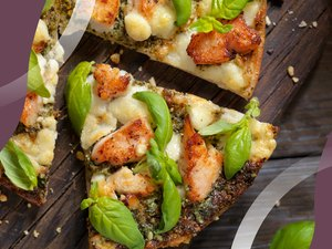 Slices of Spicy Chicken and Basil Pizza on a cutting board