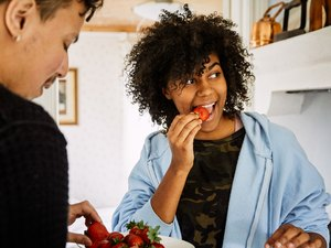 man and woman eating strawberries