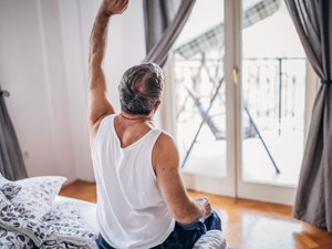 Man stretching in bed.