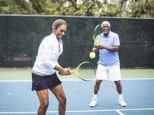 senior couple playing doubles tennis together outside