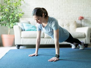 woman wearing a smartwatch and doing a push-up workout on a blue mat in her living room
