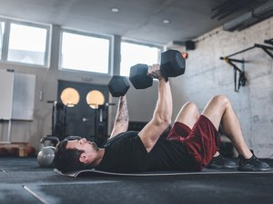 Caucasian man doing exercises for the chest using dumbbels