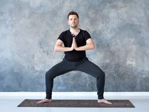 man doing a bodyweight sumo squat exercise on a yoga mat