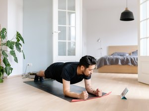 man doing forearm plank for core workout for constipation with tablet at home
