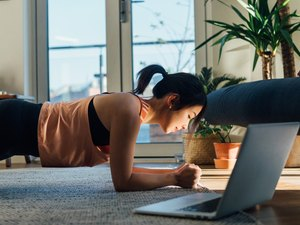 Young woman doing plank exercise in font of laptop at home