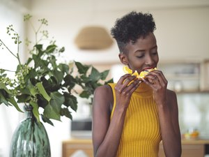 Woman eating orange in office with plant