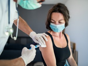 Woman with face mask getting vaccinated against covid-19 variants