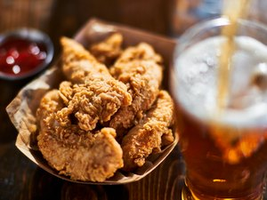 focus on fried chicken tenders in basket with beer