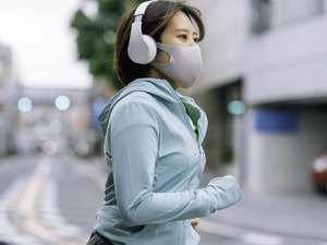 Asian woman running outdoors in a turquoise hoodie with a gray face mask and a white pair of headphones
