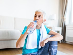 Elderly woman sitting on the sofa, exhausted after the daily training. Senior woman taking a break while exercising at home. Athletic mature woman drinking water,Having a towel around her neck