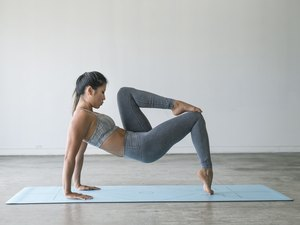 Asian woman doing an animal flow workout on a light blue yoga mat