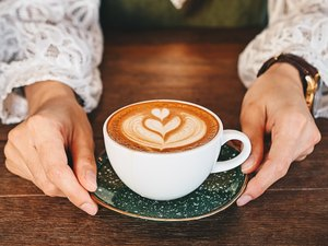 overhead shot of a woman's hands holding a cup of hot latte coffee on wooden table