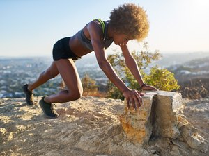 athletic young woman doing mountain climbers outside at runyon canyon